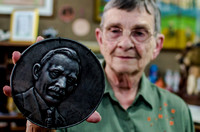 Bernice Yunker and stamped metal portrait of her grandfather.